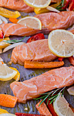 Lemon salmon with peppers, carrots, olive oil and rosemary on baking paper