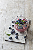 Vegan raspberry and coconut dessert with chia seeds and blueberries