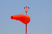 Orange windsock against a blue sky