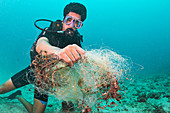 Scuba diver collecting waste fishing net