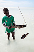 Boy with a toy boat on a beach, Zanzibar