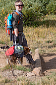 Hiker carrying dog on a hiking trail
