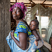 Woman with young child wrapped to her back, Liberia