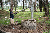 Young children pumping water from a well, Ganta, Liberia