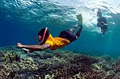 Snorkelling schoolgirl using coral reef ID guide