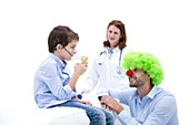 Boy using nebuliser with doctor dressed as clown