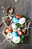 Coloured Easter eggs in a wooden bowl and wooden cutlery