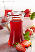 Homemade strawberry vinegar with fresh berries, apple vinegar and acacia honey