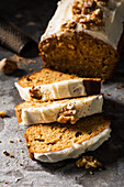 Carrot loaf cake sliced with nutmeg and grater in background