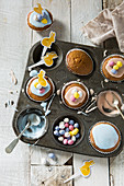 Vintage baking tray filled with cupcakes being decorated with Easter themed decorations