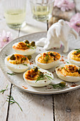 Easter deviled eggs on a serving plate with bunny