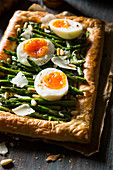 Vegetaraian asparagus tart with boiled eggs, parmesan and pinenuts
