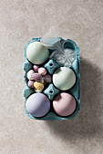 Easter Dyed Eggs in a box with chcolate mini eggs, overhead with a white feather