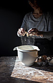 Crop human breaking egg in bowl on wooden table with flour