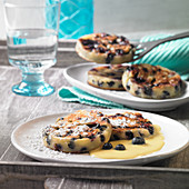 Blueberry pancakes with vanilla sauce and icing sugar