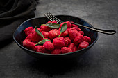 Beetroot gnocchi with sage in a black bowl