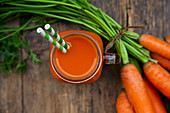 A carrot smoothie with straws in a tankard (seen from above)