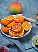 Halved bloody oranges with a wooden juicer on a ceramic plate