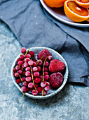 Frozen redcurrants and strawberries in a ceramic bowl