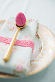 Pink egg on gold spoon and napkin on plate