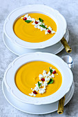 Pumpkin cream soup with feta, parsley and pomegranate seeds