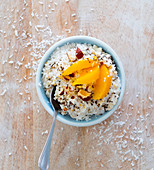 Coconut rice pudding with peaches and hazelnuts