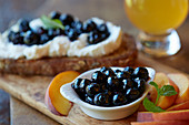 A slice of bread topped with ricotta and blueberries