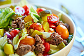 A hamburger salad with minced meat, lettuce, tomatoes, gherkins and cheese