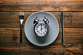Fork and knife lying on wooden tabletop near ceramic plate with mechanical alarm clock
