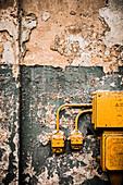 Stromkasten und Steckdosen an der Wand mit abgeblätterter Farbe