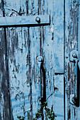 Abgeblätterte blaue Farbe an einer Holztür