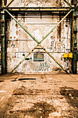 Verlassene Fabrikhalle mit abgeblätterter Farbe an der Wand