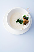 White tomato soup with a rabbit and snail skewer