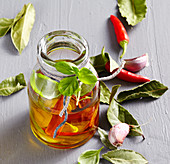 Basil-laurel oil with garlic and peperoncini in a small jar