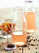 Selbstgemachter Feigenessig in Glasflaschen auf Holzuntergrund