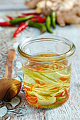 Herb oil with fresh chillies, ginger, and garlic in a mason jar