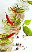 Aromatic herb oil with fresh red chillis in preserving jars
