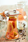 Homemade fig vinegar in jars on a wooden surface