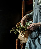 Female sitting on chair with basket of wild asparagus