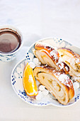 Cardamom and orange kringle slices in a dish with a slice of orange and sugared cowberries