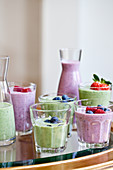 Berry smoothies and green smoothies in various cups and carafes, topped with fruit