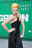 Junge blonde Frau im schwarzen Abendkleid und mit goldenem Kopftuch