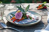 Kleiner Strauß aus Rosenblüte, Chili und Salbei auf Serviette