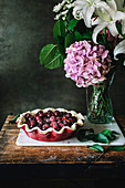 Flat lay of baked cherry pie with lattice top crust served on rustic table with green leaves around