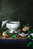 Composition of ceramic bowl with cherry and sugar and cherry kernel remover on table with green leaves