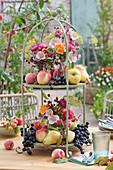 Erntedank Dekoration mit Obst und Blumensträußen auf Etagere