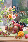 Erntedank mit Strauß aus Rosen, Hagebutten und Fetthenne in Korb mit Äpfeln