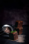 Drei Schokoladenbrownies vor dunklem Hintergrund