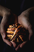 Hands showing small chocolate bun to camera in dark room