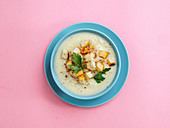 Cauliflower potato soup puree with croutons in blue bowl on pink minimalistic background